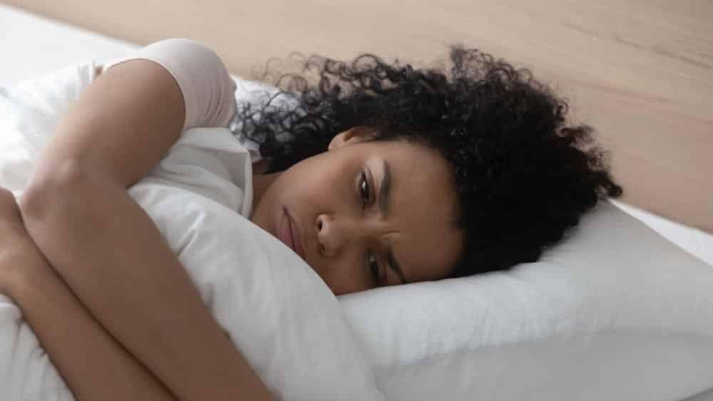 Mulher com ansiedade deitada na cama.